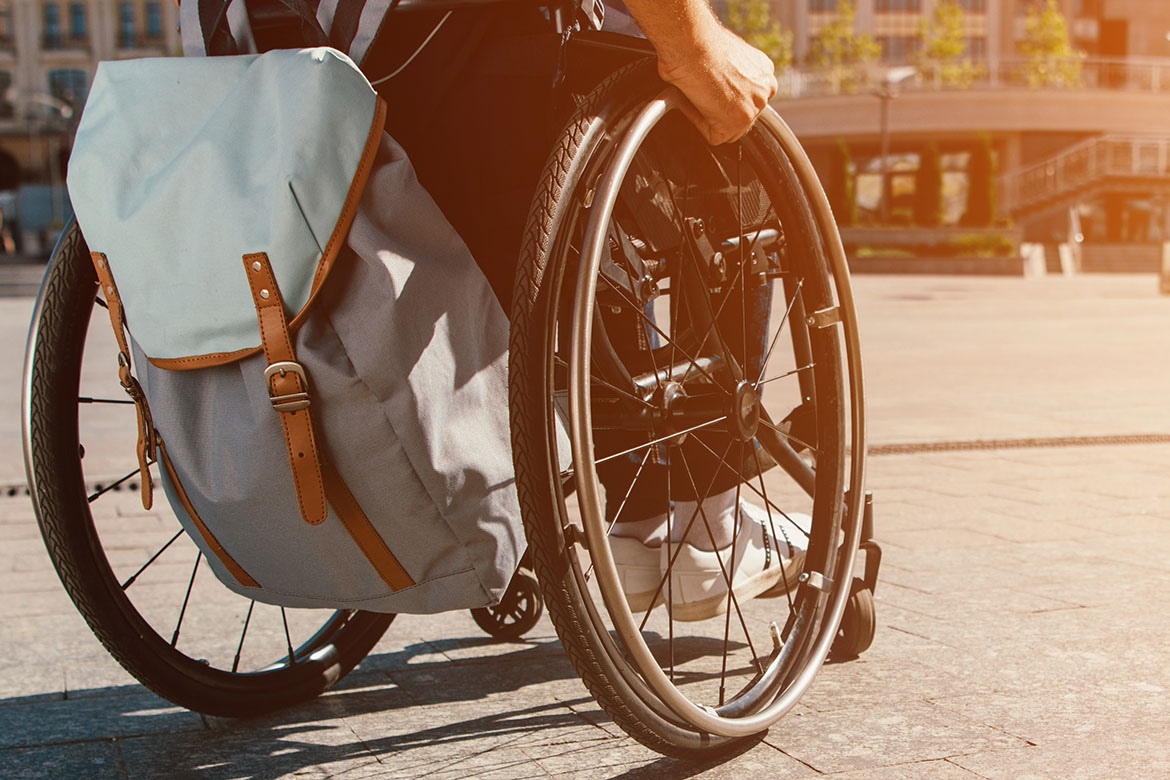 cropped panoramic view of man using wheelchair with bag on stree